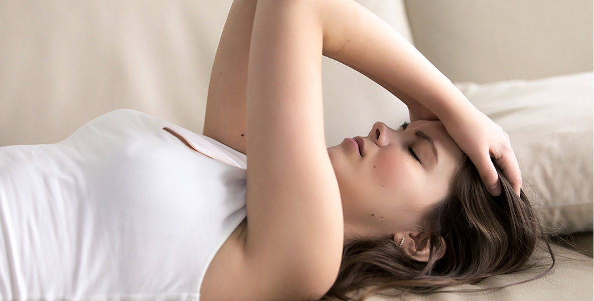 woman laying on couching holding her head in pain with a migraine