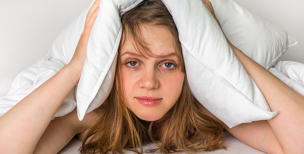 tired looking female in bed holding pillow over her ears